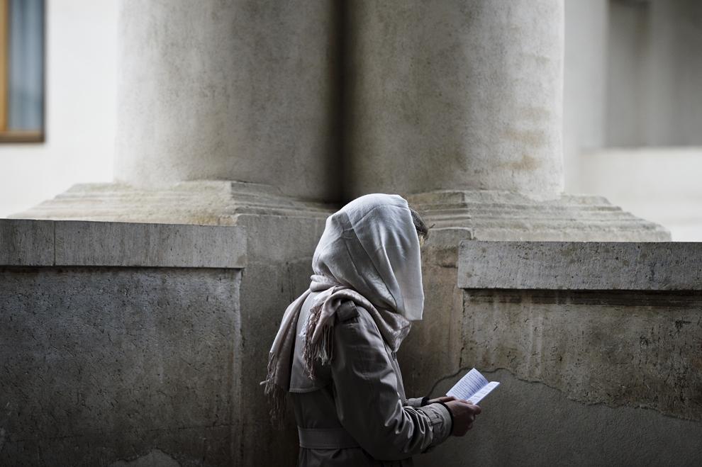 O femeie citeşte Acatistul Botezului Domnului, în timpul slujbei de Bobotează, la Catedrala Patriarhală din Bucureşti, luni, 6 ianuarie 2014.