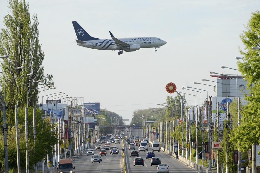 Un avion de pasageri al companiei Tarom zboară deasupra drumului naţional 1, în Otopeni, sâmbătă, 26 aprilie 2014.