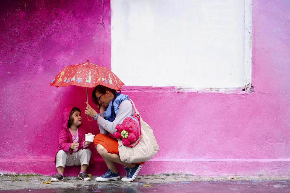 """Corina şi nepoata ei, Paulica, se feresc de ploaie, în timpul evenimentului """"Street Delivery"""", în Bucureşti, sâmbătă, 14 iunie 2014."""