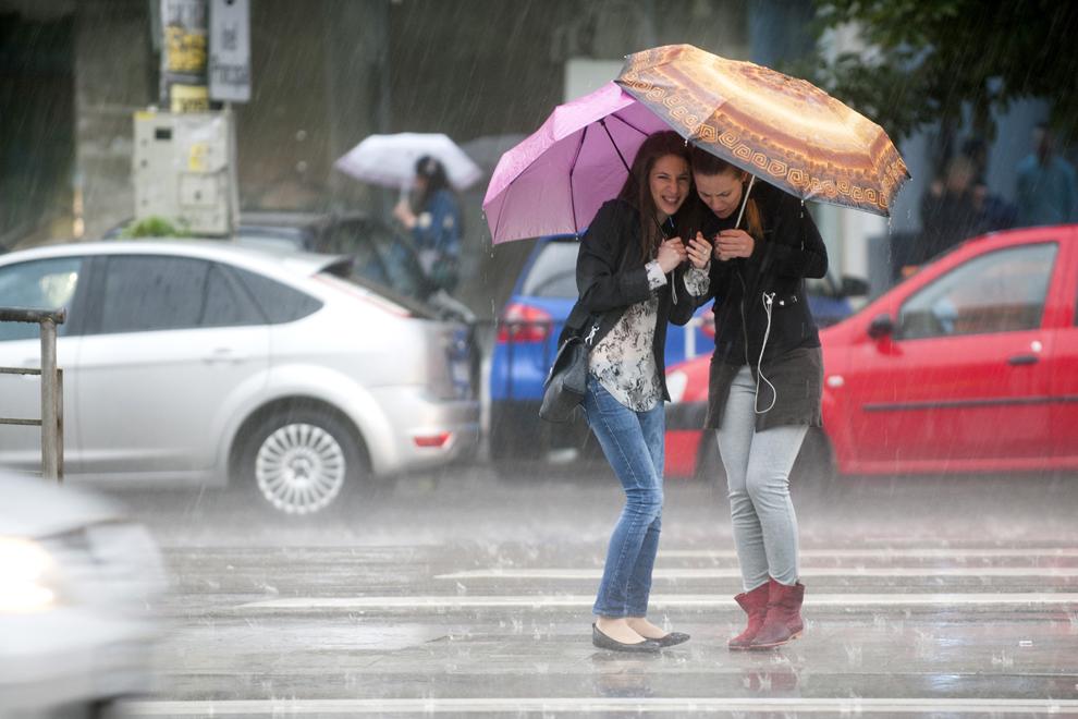 Două tinere se adăpostesc sub umbrele în timp ce aşteaptă să traverseze Şoseaua Mihai Bravu, în timpul unei ploi torenţiale de vară, în Bucureşti, vineri, 20 iunie 2014.
