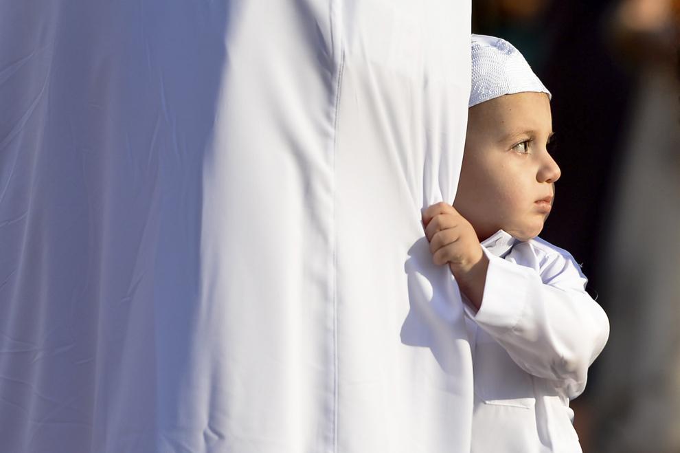 Un copil stă lângă un adult, înaintea rugăciunii din timpul sărbătorii Eid al-Fitr, care marchează încheierea lunii Ramadanului, organizată pe pista de atletism a stadionului Dinamo din Bucureşti, luni, 28 iulie 2014.