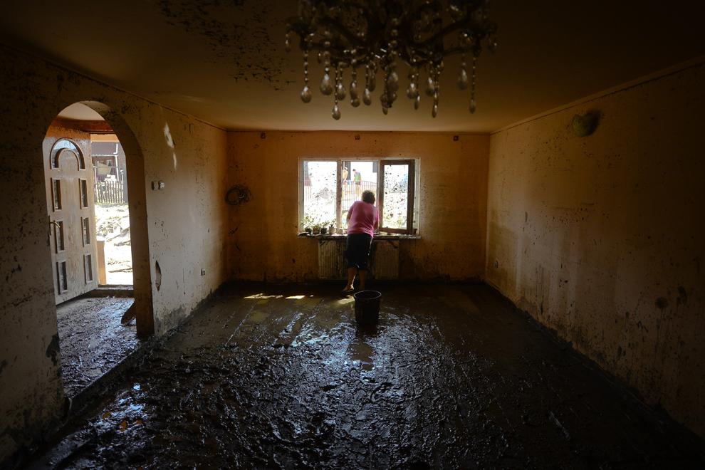 O femeie priveşte pe geamul casei afectate de viitură, în Bascov, Argeş, miercuri, 30 iulie 2014.