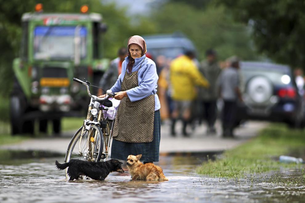 O femeie merge cu o bicicletă pe o stradă inundată, ca urmare a revărsării râului Bârzava, în oraşul Gătaia din judeţul Timiş, joi, 31 iulie 2014.