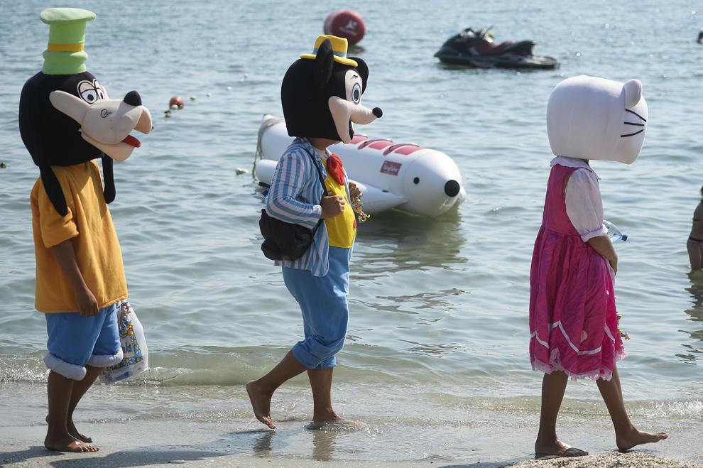 Persoane, costumate în personaje de desene animate, merg pe plaja din staţiunea Mamaia, duminică, 10 august 2014.