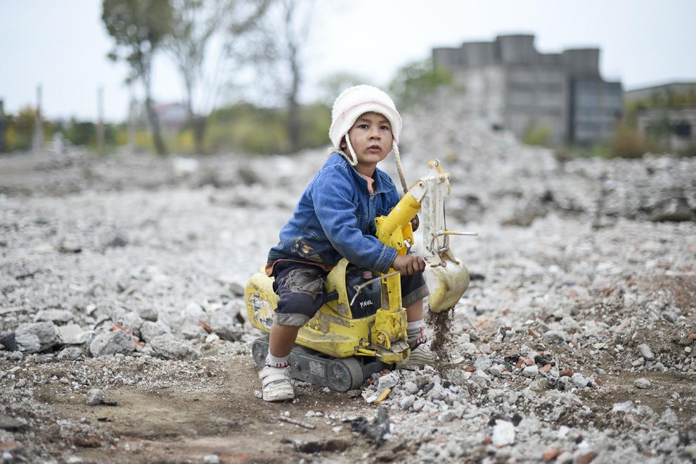 Un copil, în vârstă de patru ani se joacă în timp ce părinţii lui caută fier şi inox prin ruinele fostei hale care producea tubulatură de inox, parte a fostei Uzine Republica, în Bucureşti, joi, 2 octombrie 2014.
