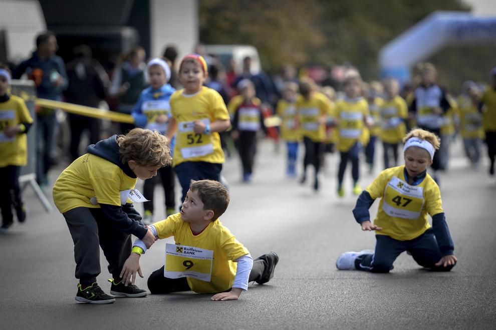 """Un copil, care a căzut, este ajutat de un alt copil să se ridice, în timpul """"Cursei Copiilor"""" din cadrul """"Maratonului Internaţional Bucureşti"""", în Bucureşti, sâmbătă, 4 octombrie 2014."""