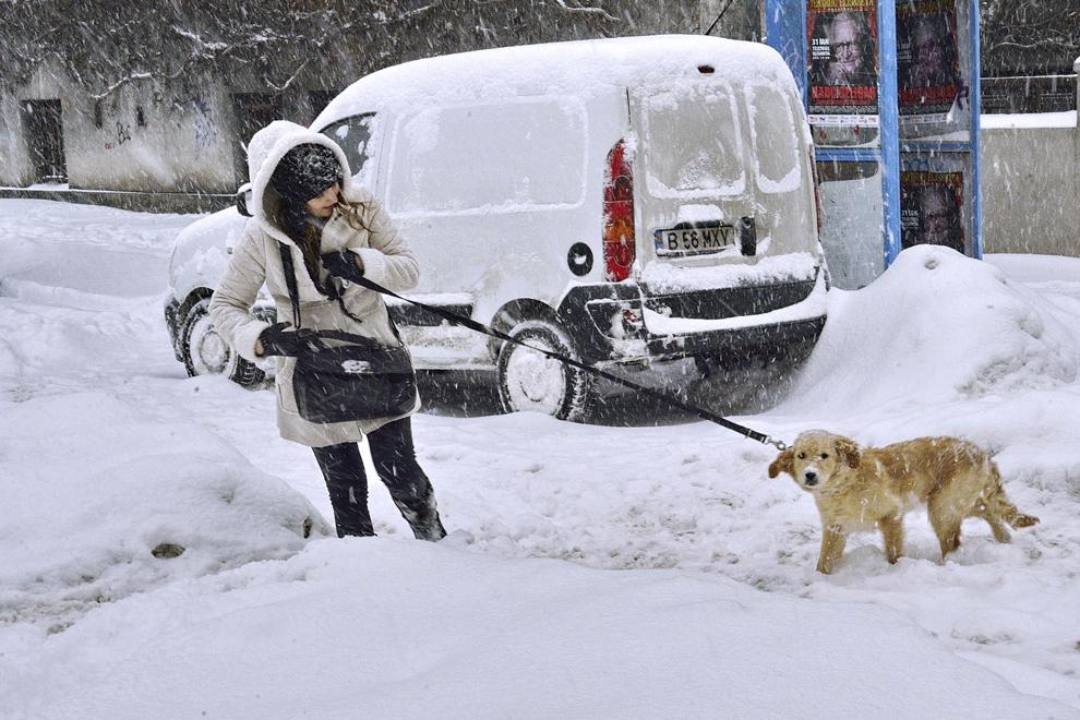O tânără merge cu un câine în lesă prin zăpadă, în Bucureşti, duminică, 26 ianuarie 2014.