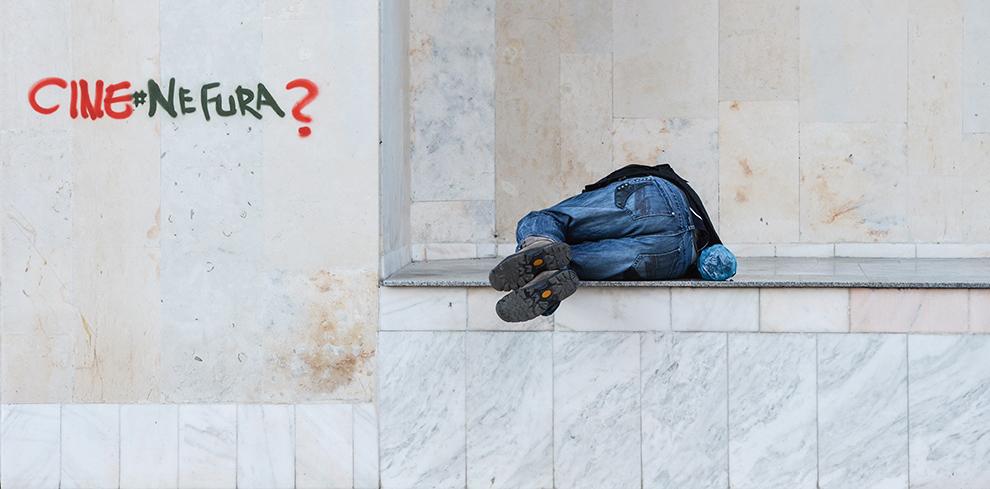 """Un bărbat doarme la intrarea unui bloc, lângă un grafitti cu mesajul """"Cine ne fură?"""", pe o stradă din Bucureşti, joi, 2 aprilie 2015."""