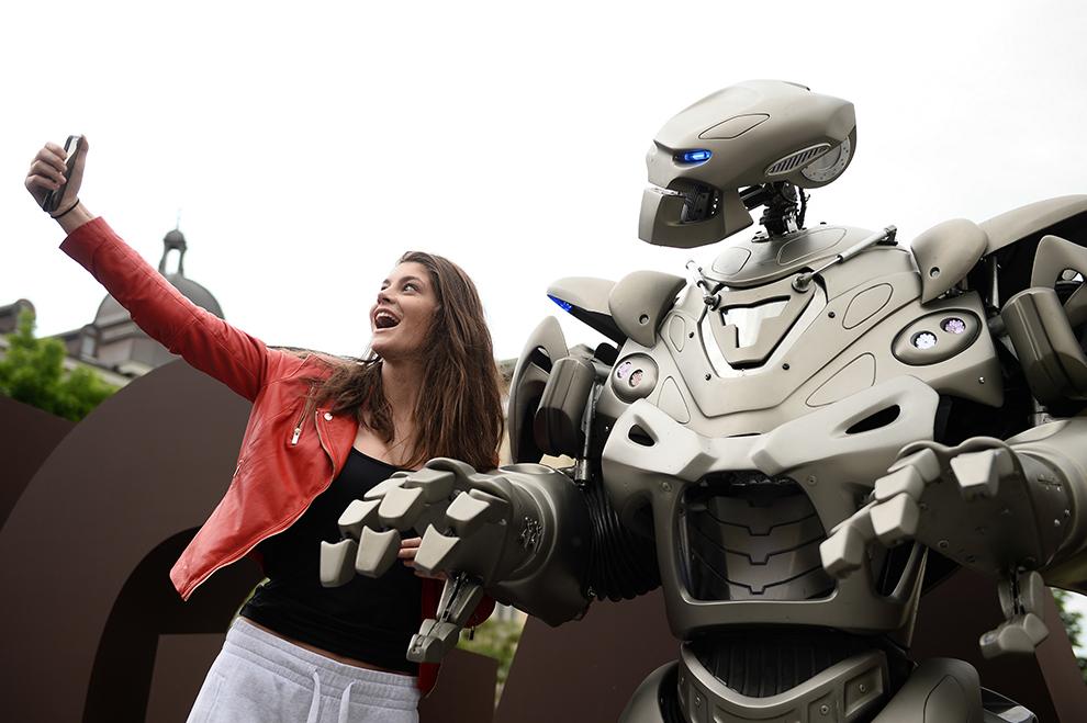 O tănără îşi face un 'selfie' cu 'Titan the Robot', un personaj robotizat folosit în spectacole live, ce este prezentat publicului în faţa Cercului Militar din Bucureşti, luni, 11 mai 2015.