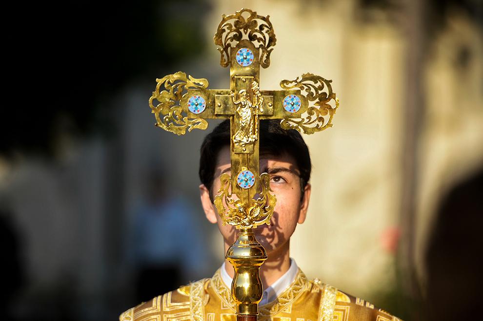 Un preot ce ţine o cruce în mână, conduce soborul de preoţi ce aduc moaştele Sfinţilor Împăraţi Constantin şi Elena la baldachinul din curtea Catedralei Patriarhale, în Bucureşti, joi, 21 mai 2015.