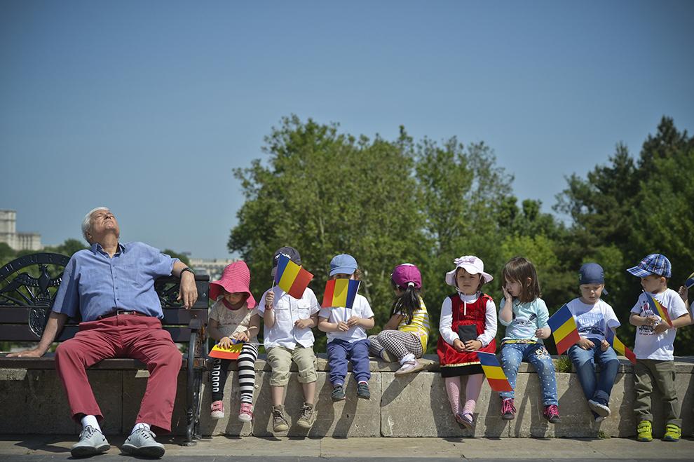 Un bărbat stă lângă un grup de copii ce flutură steaguri, în timpul unei ceremonii de comemorare a Zilei Eroilor, la Mormântul Ostaşului Necunoscut din Parcul Carol, în Bucureşti, joi, 21 mai 2015.