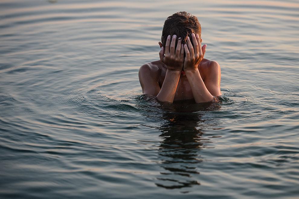 Alex, 12 ani, se scaldă în apa lacului Morii din Bucureşti, joi, 9 iulie 2015.