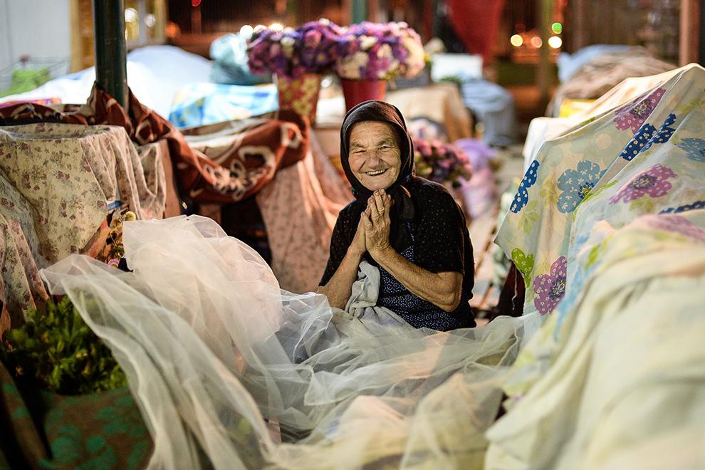 Maria Nedelcu, 71 ani, vânzătoare de legume, reacţionează atunci când este fotografiată, în piaţa Râmnicu Sărat din Bucureşti, vineri, 7 august 2015.