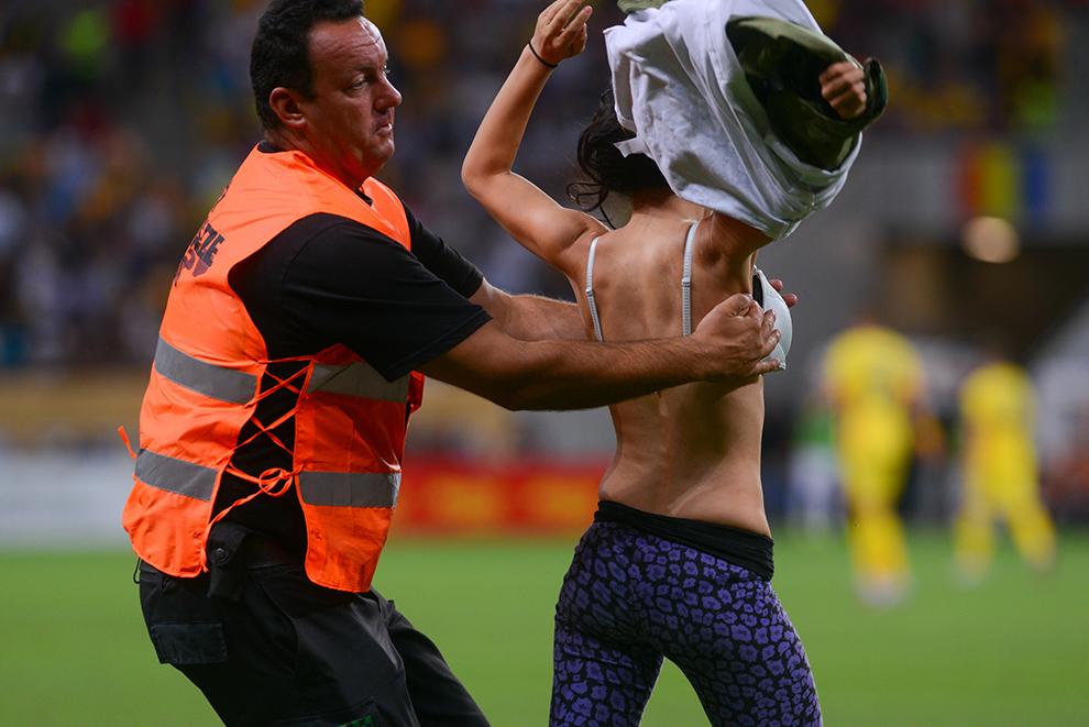 O tânără ce a pătruns pe gazon este îndepărtată de agenţii de securitate, în timpul meciului România - Grecia, din grupa F a preliminariilor Campionatului European din 2016, pe stadionul Naţional Arena din Bucureşti, luni, 7 septembrie 2015.
