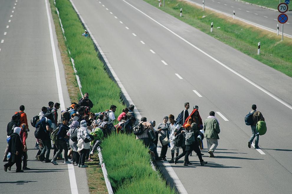 Un grup de refugiaţi forţează un baraj al poliţiei şi fug pe autostradă, în Roszke, localitate aflată la graniţa dintre Serbia şi Ungaria, miercuri, 9 septembrie 2015.