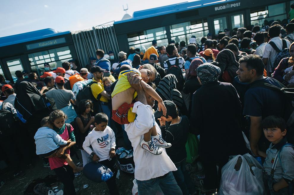 Refugiaţi aşteaptă să fie preluaţi de poliţia ungară pentru a fi transportaţi la un centru de tranzit din Roszke, localitate aflată la graniţa dintre Serbia şi Ungaria, miercuri, 9 septembrie 2015.