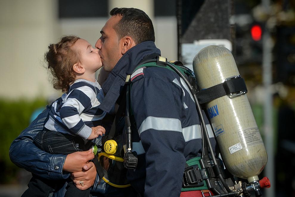 """Un pompier îşi sărută copilul înaintea ceremoniilor militare şi religioase, organizate în faţa """"Monumentului Eroilor Pompieri"""" din Bucureşti, cu prilejul Zilei Pompierilor din România, duminică, 13 septembrie 2015."""