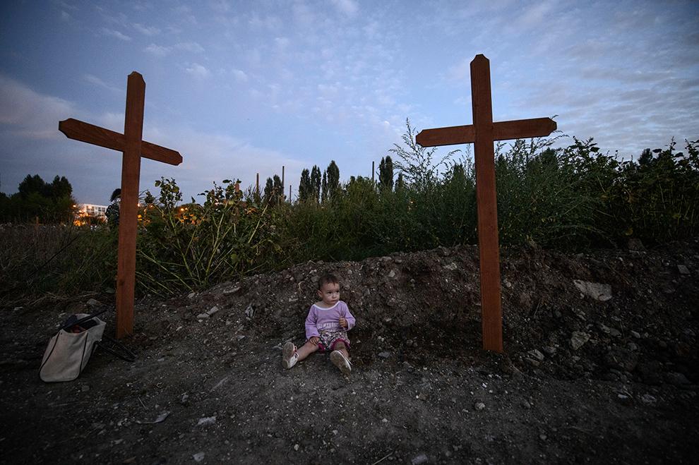Un copil se joacă lângă o cruce de lemn în timpul unei slujbe de sfinţire, ce are loc pe terenul presupus a fi destinat construirii unei moschei, în Bucureşti, sâmbătă, 19 septembrie 2015.