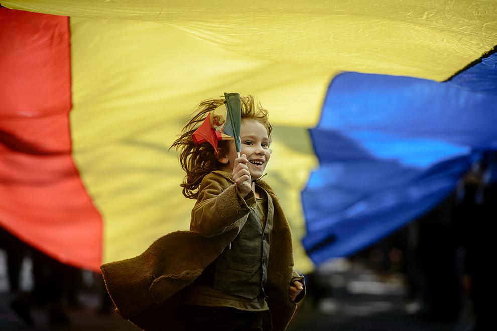 Un copil, ce ţine în mână un steguleţ, aleargă sub un steag tricolor, lung de 150 de metri, în timpul unei manifestaţii organizate cu ocazia aniversarii a 94 de ani de la naşterea Majestaţii Sale Regele Mihai I al României, in Bucureşti, duminică, 25 octombrie 2015.