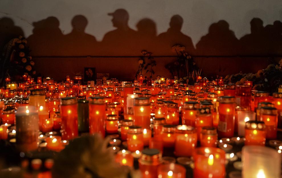 Umbrele persoanelor ce ţin un moment de reculegere se proiectează pe un perete, în spatele candelor aprinse în memoria victimelor incendiului din Clubul Colectiv din Bucureşti, sâmbătă, 31 octombrie 2015.