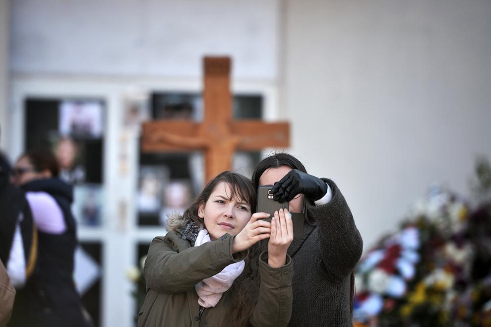 Doua tinere se fotografiază cu telefonul mobil, în timpul comemorarii victimelor incendiului din clubul Colectiv, în Bucureşti, luni, 30 noiembrie 2015.