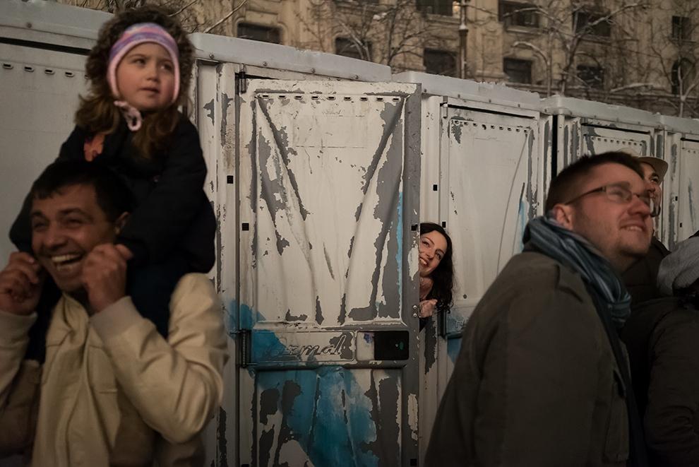 O tânără priveşte jocul de artificii dintr-o toaletă ecologică, în Piaţa Constituţiei din Bucureşti, joi, 1 ianuarie 2015.