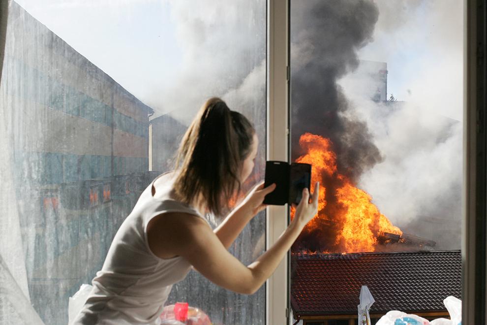 O studentă din Căminul 12 al Complexului Studenţesc din Timişoara filmează de la geam incendiul izbucnit într-un restaurant din Complex, vineri, 16 ianuarie 2015.