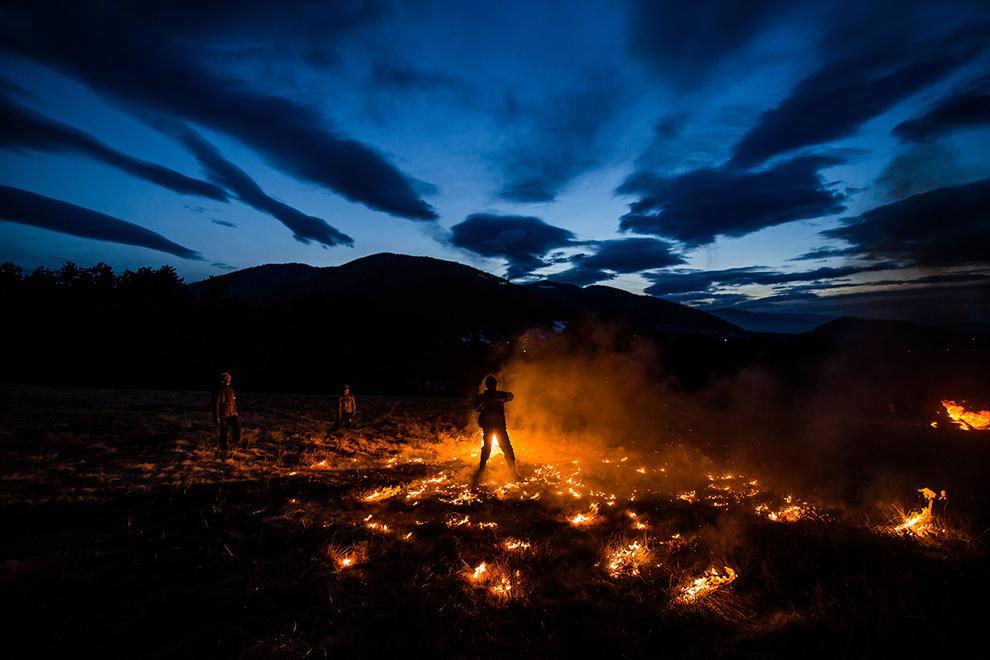 Un tânăr dă foc unui cauciuc pe care apoi îl învârte în aer, în noaptea Lăsatului de Sec, ultima zi dinaintea postului Paştelui, pe dealul de lângă comuna Poplaca, judeţul Sibiu, duminică, 22 februarie 2015.