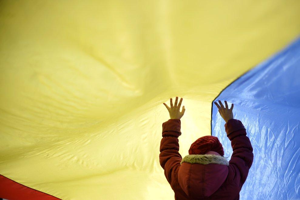 """Un copil se joaca sub un steag tricolor in timpul """"Marii Adunari Centenare"""", manifestatie dedicata implinirii a 100 de ani de la unirea Basarabiei cu Romania, duminica, 25 martie 2018, in Chisinau,"""