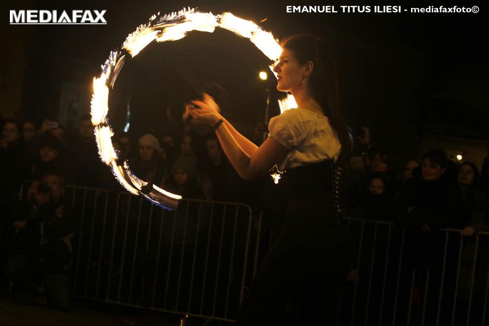 O tanara sustine un numar de jonglerie cu foc, cu ocazia celebrarii Orei Pamantului, in Piata Libertatii din Timisoara, sambata, 24 martie 2018.
