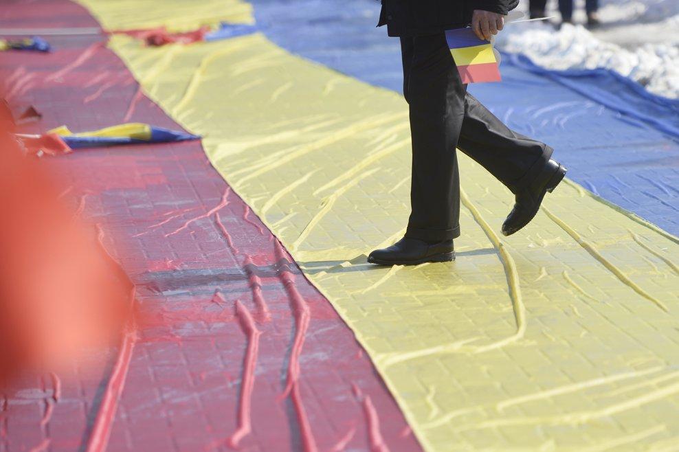 """Un barbat paseste pe un steag tricolor in timpul evenimentului """"Marea Adunare Centenara"""", manifestatie dedicata implinirii a 100 de ani de la unirea Basarabiei cu Romania, duminica, 25 martie 2018, in Chisinau, Republica Moldova. ANDREEA ALEXANDRU / MEDIAFAX FOTO"""