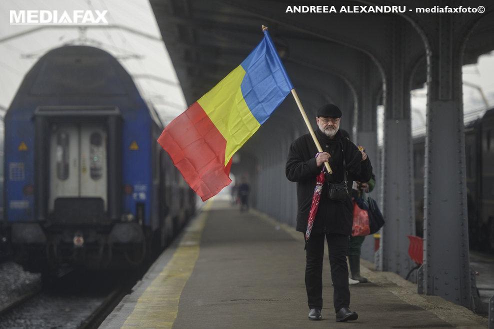 Un barbat flutura un steag tricolor pe un peron din Gara de Nord, sambata, 20 ianuarie 2018. Zeci de oameni au ajuns sambata, in jurul pranzului, in Gara de Nord, pentru a participa la mitingul organizat impotriva modificarilor justitiei. ANDREEA ALEXANDRU / MEDIAFAX FOTO