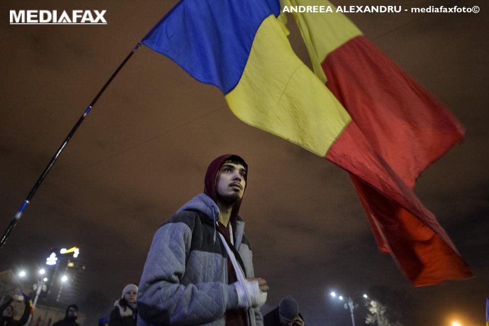 Un barbat flutura un steag tricolor in timpul unui protest fata de proiectele adoptate de Executiv privind gratierea si modificarea Codurilor penale, in Piata Victoriei din Bucuresti,  sambata, 4 februarie 2017. Peste 150.000 de oameni au protestat in fata Guvernului Romaniei. ANDREEA ALEXANDRU / MEDIAFAX FOTO