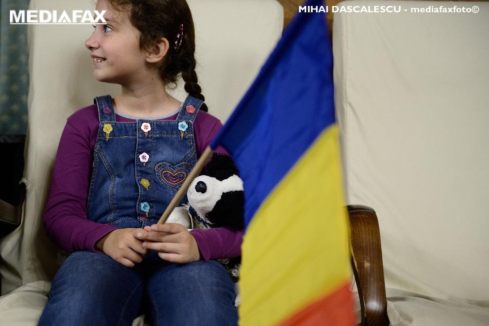 O fetita cu un steag tricolor si jucaria preferata in brate, sta asezata, marti 1 Decembrie 2015, intr-un fotoliu aflat in Palatul Victoria din Bucuresti. Guvernul Romaniei si-a deschis portile, ca in fiecare an, pentru vizitatori, parte a traditiei in sarbatorirea Zilei Nationale a Romaniei. MIHAI DASCALESCU / MEDIAFAX FOTO