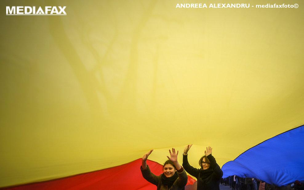 Doua tinere se plimba pe sub un steag tricolor in timpul unui protest fata de modul de organizare a celui de-al doilea tur de scrutin al alegerilor prezidentiale, dar si fata de victoria socialistului Igor Dodon, organizat de Organizatia Onoare, Demnitate si Patrie (ODIP), in Chisinau, Moldova, luni, 14 noiembrie 2016. ANDREEA ALEXANDRU / MEDIAFAX FOTO