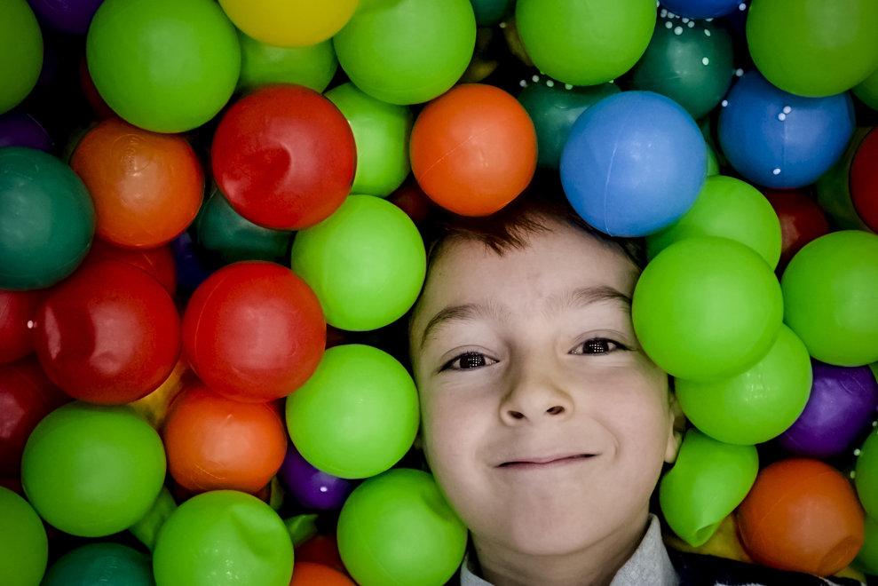 """Un copil zambeste in timp ce face o baie intr-o piscina cu bile colorate, in timpul evenimentului """"Craciunul se petrece in marea familie a Armatei Romaniei"""", organizat de Ministerul Apararii Nationale, in Bucuresti, vineri, 14 decembrie 2018. ANDREEA ALEXANDRU / MEDIAFAX FOTO"""