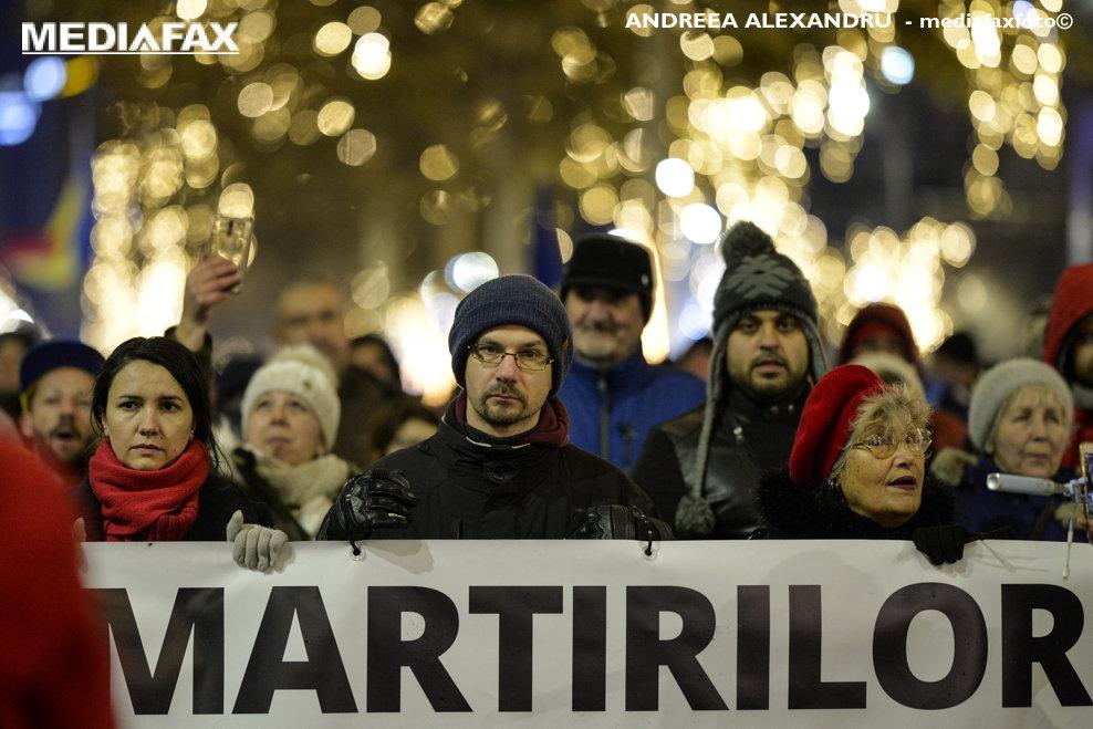 Persoane marsaluiesc cu un banner in fata, in timpul unui eveniment de comemorare a victimelor Revolutiei din decembrie 1989, in Bucuresti, sambata, 22 decembrie 2018. ANDREEA ALEXANDRU / MEDIAFAX FOTO