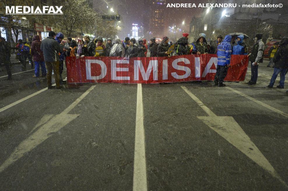"""Persoane afiseaza un banner cu mesajul """"DEMISIA"""" in timpul unui protest  fata de mai multe masuri si  propuneri ale Parlamentului,  privind proiectul de modificare a legilor justitiei, sambata, 20 ianuarie 2018, in Bucuresti. ANDREEA ALEXANDRU / MEDIAFAX FOTO"""