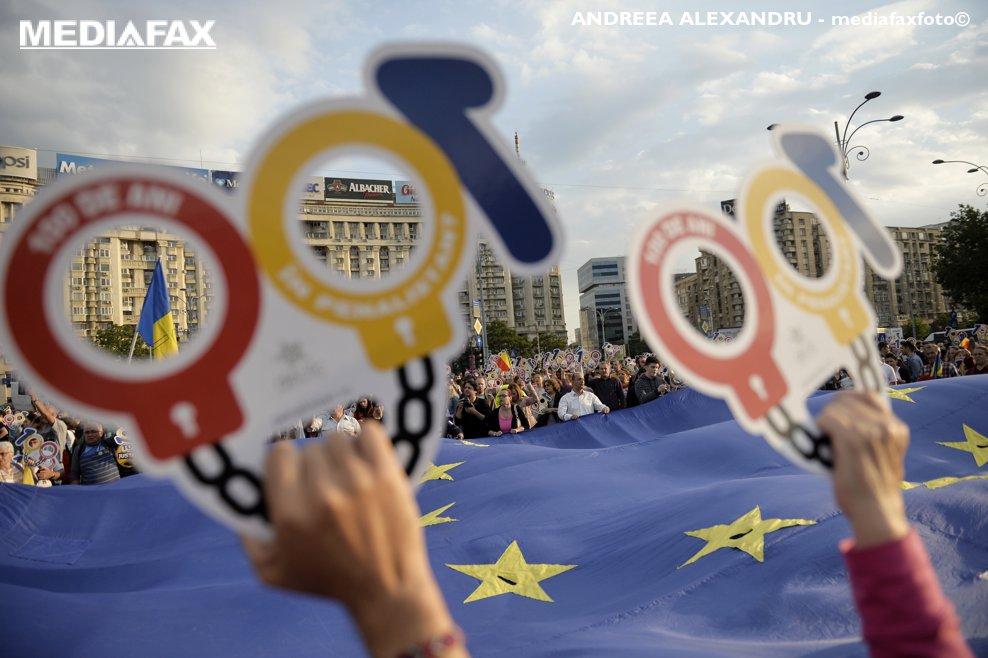 """Persoane afiseaza pancarte cu mesajul """"100 de ani in Penalistan"""", in timpul unui protest intitulat """"Vrem Europa, nu dictatura"""", in Piata Victoriei din Bucuresti, sambata, 12 mai 2018. Mii de persoane s-au adunat in Piata Victoriei, din Bucuresti, pentru a protesta fata de coalitia de guvernare. ANDREEA ALEXANDRU / MEDIAFAX FOTO"""