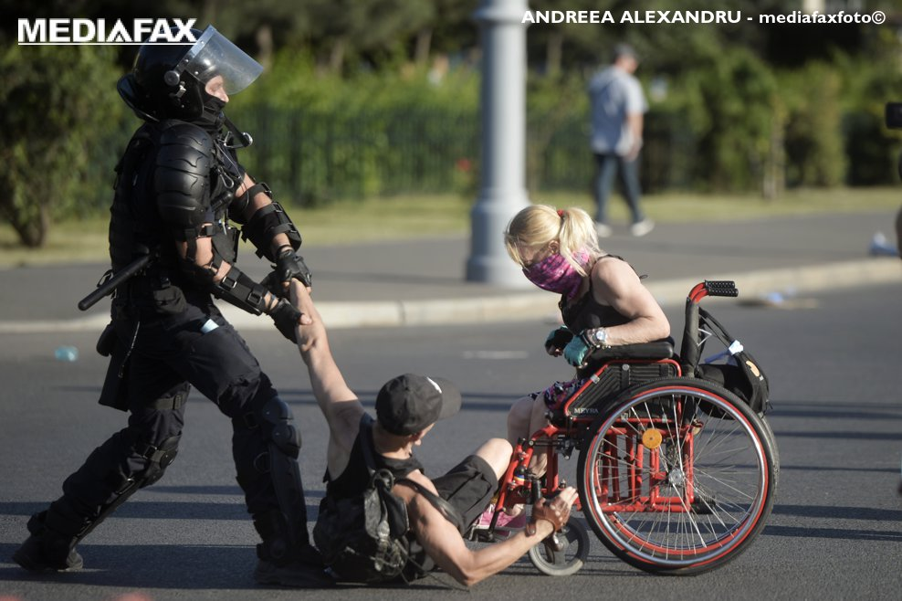 """Un jandarm incearca sa ridice de pe asfaltul din fata sediului guvernului, un protestatar ce insoteste o persoana cu dezabilitati aflata intr-un scaun cu rotile, in timpul unui protest al romanilor cu rezidenta in strainatate, """"Protestul Diasporei"""", vineri 10 august 2018, in Piata Victoriei din Bucuresti. ANDREEA ALEXANDRU / MEDIAFAX FOTO"""