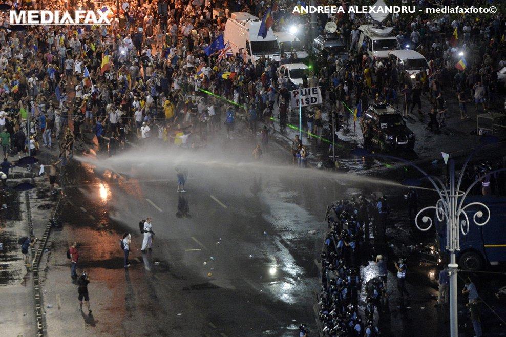 """Protestatarii sunt indepartati de sediul guvernului cu tunul cu apa sub presiune,  in timpul mitingului de protest al cetatenilor romani rezidenti in strainatate, """"Protestul Diasporei"""", impotriva guvernului si al PSD, vineri 10 august 2018, in Piata Victoriei din Bucuresti. ANDREEA ALEXANDRU / MEDIAFAX FOTO"""