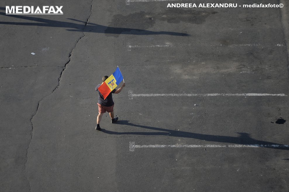 """O persoana flutura un steag tricolor in timp ce soseste la mitingul de protest al cetatenilor romani rezidenti in strainatate, """"Protestul Diasporei"""", impotriva guvernului si al PSD, sambata, 11 august 2018, in Piata Victoriei din Bucuresti. ANDREEA ALEXANDRU / MEDIAFAX FOTO"""