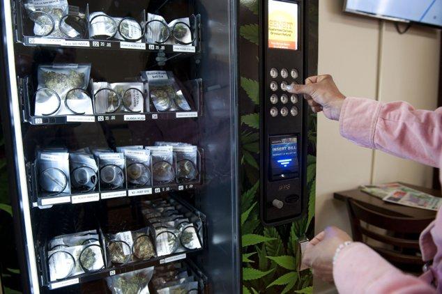 """Acest aparat de comercializat marijuana se găseşte în Vancouver, Canada. Pentru 4 dolari canadieni, aparatul eliberează o pungă de plastic umplută cu varietatea """"Cotton Candy"""". Varianta """"Purple Kush"""" costă 6 dolari canadieni."""