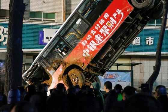 Imaginea articolului Momentul în care un autobuz plin cu pasageri este înghiţit de un crater apărut în asfalt, în China. Şase oameni au murit. VIDEO