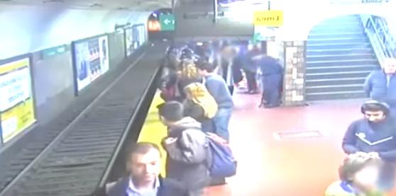 VIDEO | Femeie salvată în ultimul moment, după ce un bărbat a leşinat şi a împins-o pe şinele de la metrou